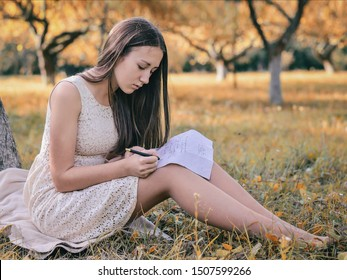 A young beautiful brunette girl with long hair in a summer dress sits on a lawn near a tree and writes a letter to her beloved man. Letter to a soldier. Romance writing a letter. Girl in a garden