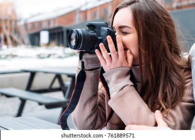 Young beautiful brunette girl photographer makes photos outdoor in cafe in winter cold weather