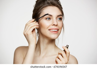 Young beautiful brunette girl smiling looking at camera painting eyebrows with mascara over white background. Beauty spa and cosmetology.
