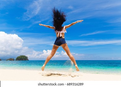 Young beautiful brunette with hair flying in the wind having fun on a tropical beach with her back to the viewer. Summer vacation concept.