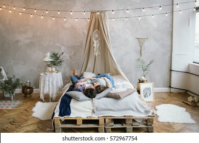 Young beautiful brunette hipster couple having fun on handmade bed with dreamcatcher