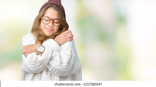 Young beautiful brunette hipster woman wearing glasses and winter hat over isolated background Hugging oneself happy and positive, smiling confident. Self love and self care