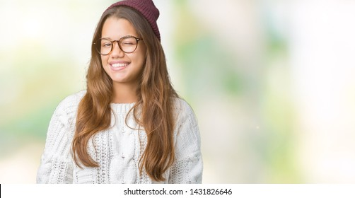 Young beautiful brunette hipster woman wearing glasses and winter hat over isolated background winking looking at the camera with sexy expression, cheerful and happy face.