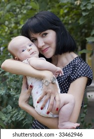 Young beautiful brunette holds on hands of baby
