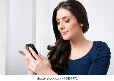 Young beautiful brunette lady touching and browsing her smart phone at home