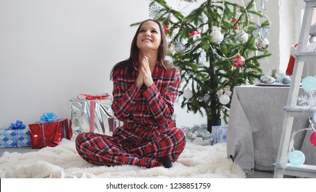 Young beautiful brunette in pajamas sits on a rug makes a wish near a Christmas fir-tree.