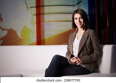 Young beautiful brunette television announcer at studio during live broadcasting.Female TV director at editor in studio.Recording at TV studio with television anchorwoman. TV NEWS studio