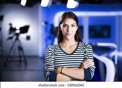 Young beautiful brunette television announcer at studio standing next to the camera.TV director at editor in studio.Recording at TV studio with television anchorwoman. TV NEWS studio behind the scenes