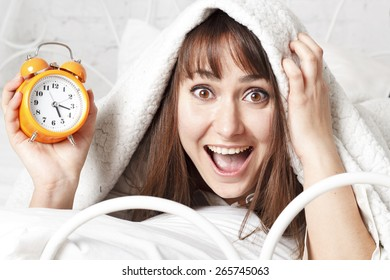 Young beautiful brunette woman in bed with clock
