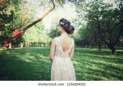 Young beautiful brunette woman in blooming spring garden. portrait from the back of a gentle bride
