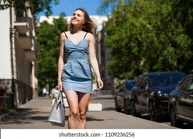 Young beautiful brunette woman in a blue short dress walking on the road, summer street outdoors
