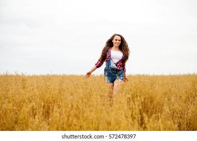 Young beautiful brunette woman in blue jeans short walking in a field, summer outdoors