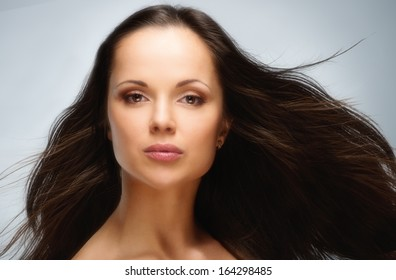 Young beautiful brunette woman with brown eyes and long waving hair