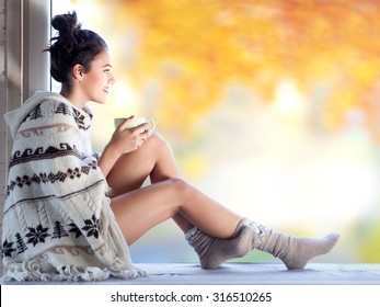 Young beautiful  brunette woman with cup of coffee wearing knitted nordic print poncho sitting home by the window. Blurred  garden fall background.