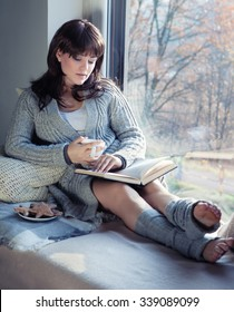 Young beautiful brunette woman with cup of coffee and gingerbread wearing knitted cardigan reading book relaxing by the window. Home chill out concept.