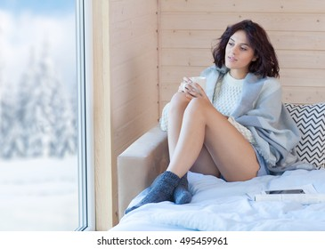 Young beautiful brunette woman with cup of coffee sitting home on the bed by the window. Winter snow landscape view. Lazy day off concept
