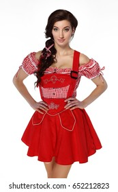 Young beautiful brunette woman dressed in red traditional Bavarian dress on white background