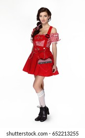 Young beautiful brunette woman dressed in red traditional Bavarian costume on white background