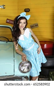 Young beautiful brunette woman dressed in a blue dress with polka dots with a bow on her head stands leaning on a blue car