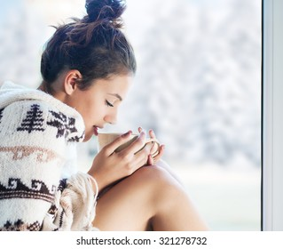 Young beautiful brunette woman drinking cup of coffee wearing knitted nordic print poncho sitting home by the window. Blurred winter snow tree background.