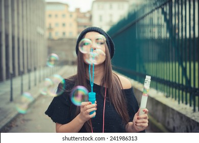 young beautiful brunette woman girl blowing bubbles soup outdoor