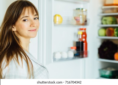 e6d0a399ed3b Young beautiful brunette woman in pajamas searching for food in the fridge  and looking at camera