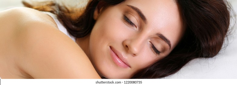 Young beautiful brunette woman portrait lying in bed sleeping late in the morning after hard work day tired. Fresh bedclothes furnishing shop new day weekend day off washing or laundry concept