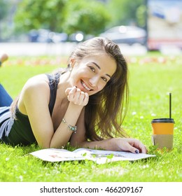 Young beautiful brunette woman reading a womens magazine on the green grass in the summer park