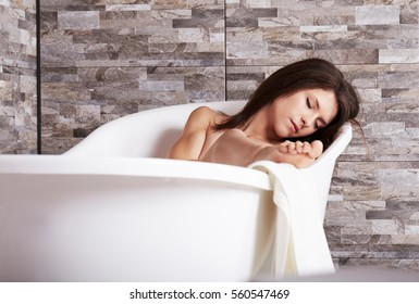 young beautiful brunette woman relaxing in bathtub