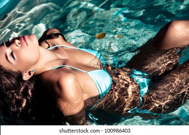 young beautiful brunette woman resting in the swimming pool on the sunny day