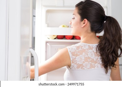 young beautiful brunette woman searching for food in the fridge