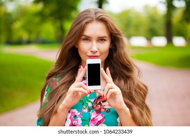 Young beautiful brunette woman showing your smartphone screen, summer park outdoors