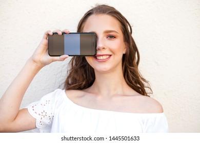 Young beautiful brunette woman showing your smartphone screen