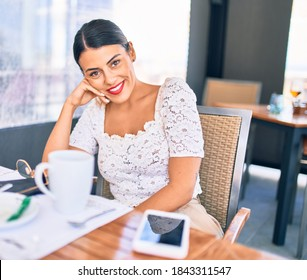 Young beautiful brunette woman smiling happy and confident. Sitting with smile on face at restaurant