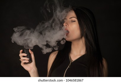 Young beautiful brunette woman smoking, vaping e-cigarette with smoke on black background.