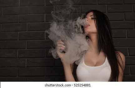 Young beautiful brunette woman smoking, vaping e-cigarette with smoke on black background.