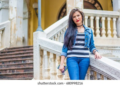 Young beautiful brunette woman standing on stairs.