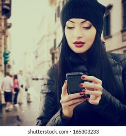 Young beautiful brunette woman touching and browsing her smart phone over city background, toned