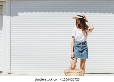 Young beautiful brunette woman wearing blue denim mini skirt, white t-shirt, wicker straw bag and boater hat walking near white roller door. Trendy casual summer or spring outfit. Street fashion.
