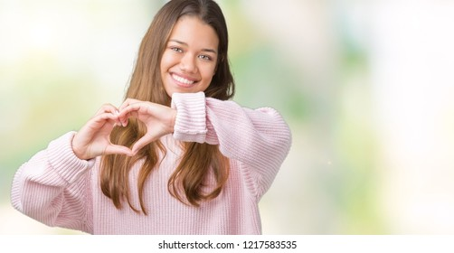 Young beautiful brunette woman wearing pink winter sweater over isolated background smiling in love showing heart symbol and shape with hands. Romantic concept.