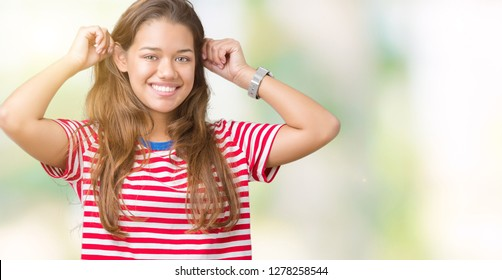 Young beautiful brunette woman wearing stripes t-shirt over isolated background Smiling pulling ears with fingers, funny gesture. Audition problem
