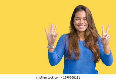Young beautiful brunette woman wearing blue sweater over isolated background showing and pointing up with fingers number seven while smiling confident and happy.