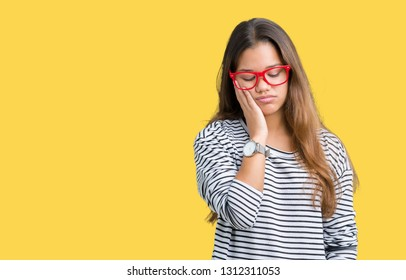 Young beautiful brunette woman wearing stripes sweater and red glasses over isolated background thinking looking tired and bored with depression problems with crossed arms.