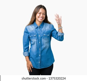 Young beautiful brunette woman wearing blue denim shirt over isolated background Waiving saying hello happy and smiling, friendly welcome gesture