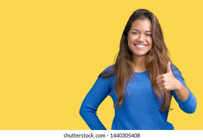 Young beautiful brunette woman wearing blue sweater over isolated background doing happy thumbs up gesture with hand. Approving expression looking at the camera showing success.