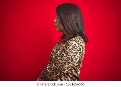 Young beautiful brunette woman wearing a leopard jacket over red isolated background looking to side, relax profile pose with natural face with confident smile.