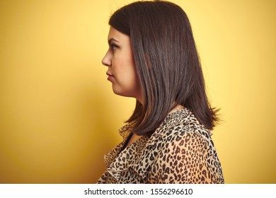 Young beautiful brunette woman wearing leopard shirt over yellow isolated background looking to side, relax profile pose with natural face with confident smile.