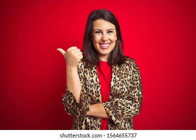 Young beautiful brunette woman wearing a leopard jacket over red isolated background smiling with happy face looking and pointing to the side with thumb up.
