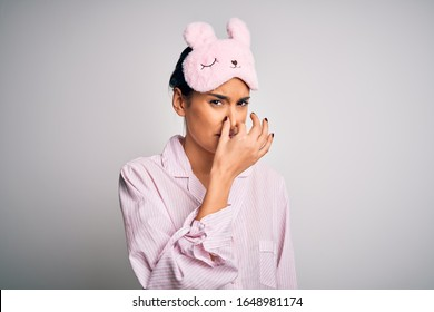 Young beautiful brunette woman wearing pajama and sleep mask over white background smelling something stinky and disgusting, intolerable smell, holding breath with fingers on nose. Bad smell