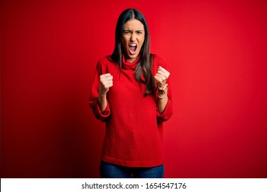 Young beautiful brunette woman wearing casual sweater over isolated red background angry and mad raising fists frustrated and furious while shouting with anger. Rage and aggressive concept.